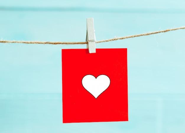 Czerwoni serca ustawiający na sznurku nad błękitnym tłem. koncepcja walentynki. miejsce na tekst