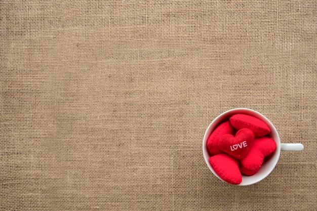 Czerwoni serca w filiżance kawy na workowym tekstury tle z kopii przestrzenią