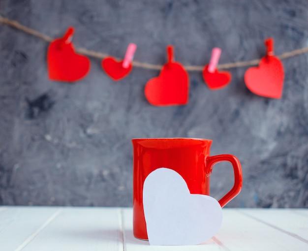 Czerwoni serca wychodzi z filiżanki na czerwonym tle. koncepcja walentynek kobiet. miejsce na tekst, miejsce.