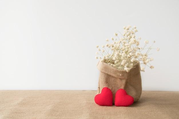 Czerwoni serca z kwiatami w workowej torbie z kopii przestrzenią na białym tle