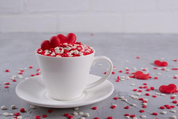 Czerwoni słodcy cukrowego cukierku serca w filiżance kawy. dekoracja koncepcji miłości i walentynki.
