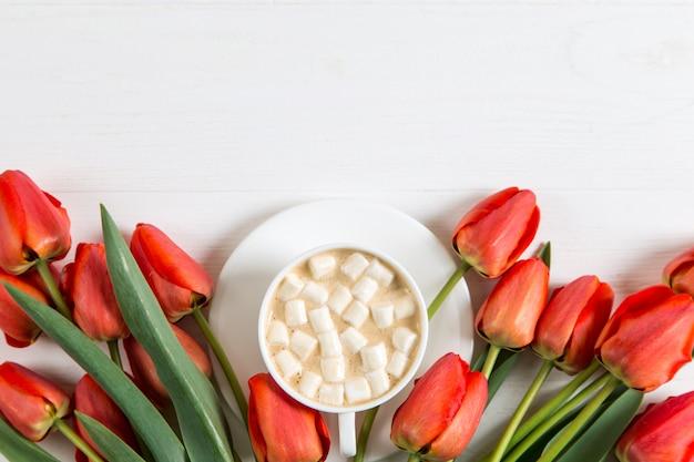 Czerwoni tulipany i filiżanka kawy z marshmallows na bielu. przygotowanie pocztówki na wiosenne wakacje. skopiuj miejsce