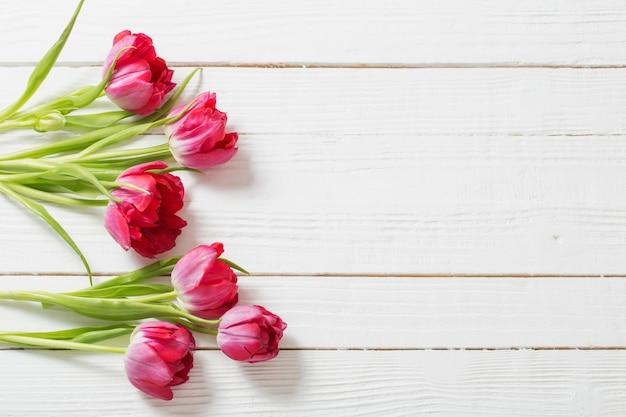 Czerwoni tulipany na białym drewnianym tle