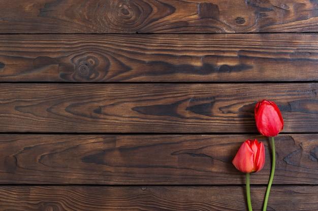 Czerwoni tulipany na ciemnym drewnianym stole