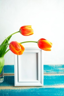 Czerwoni tulipany w szklanej wazie z pustą ramą