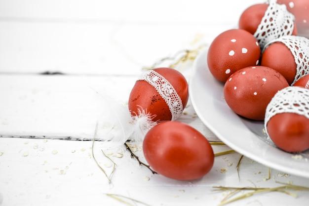 Czerwoni wielkanocni jajka na białym talerzu