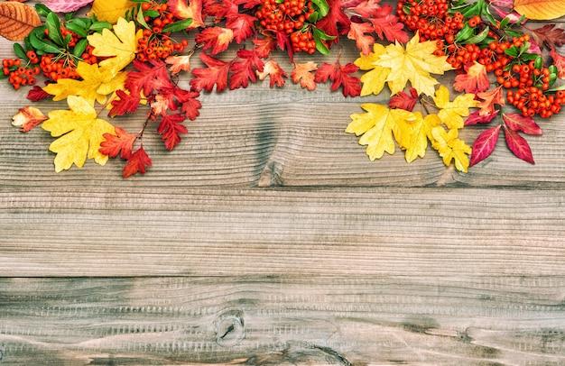 Czerwoni żółci liście na drewnianym tle. jesień