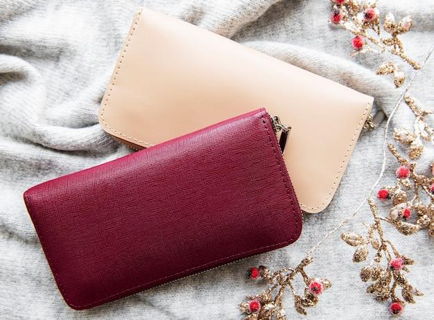 Czerwono-beżowe skórzane portfele na szarej dzianinowej powierzchni
