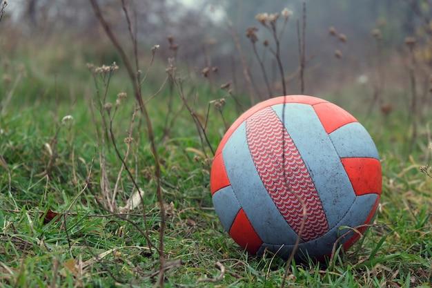 Czerwono biała piłka na trawie w parku z mglistą ponurą deszczową pogodą.