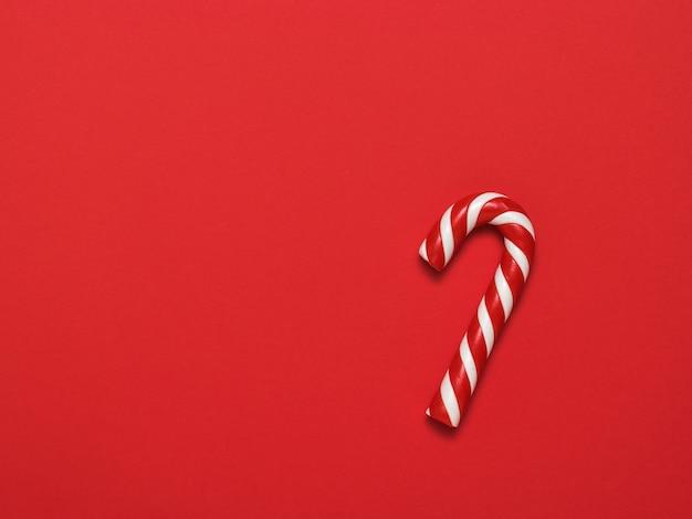 Czerwono-biała słodycz bożego narodzenia na jasnym czerwonym tle