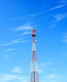Czerwono-biała wieża komunikacyjna z pięknym jasnym niebem
