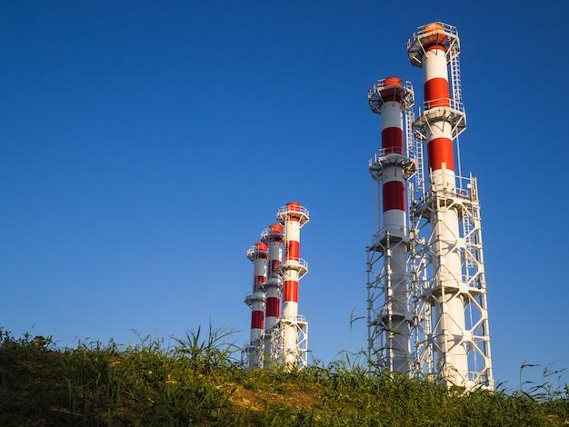 Czerwono-białe kominy kotłowni na tle błękitnego nieba.