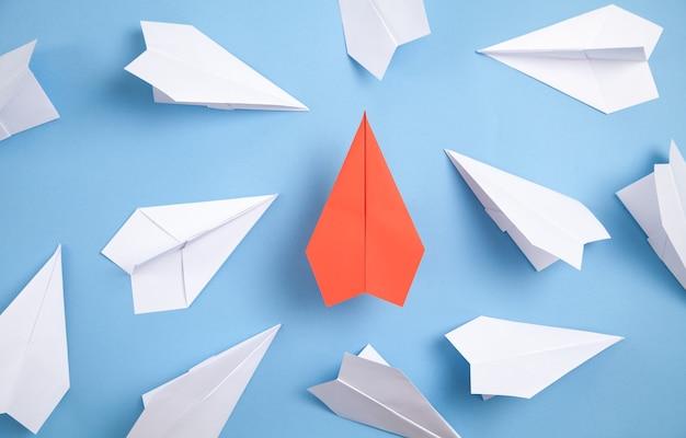 Czerwono-białe papierowe samoloty na niebieskim tle. przywództwo. praca w zespole