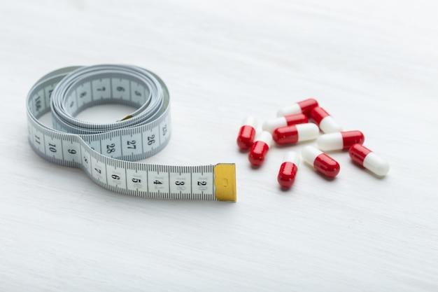 Czerwono-białe tabletki odchudzające leżą na białym stole obok miarki. koncepcja odchudzania za pomocą leków.