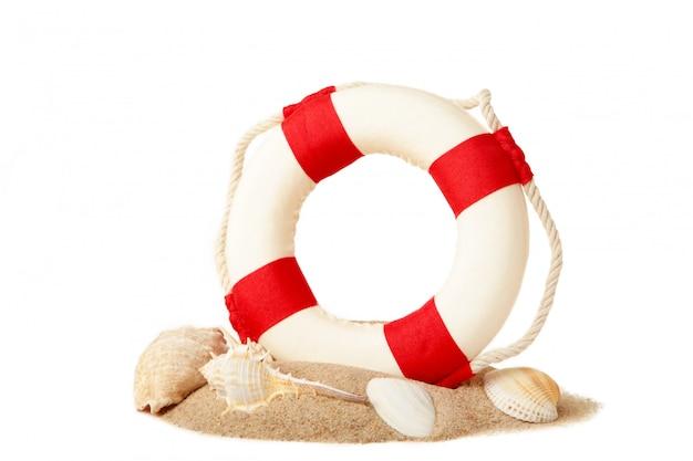 Czerwono biały koło ratunkowe z piaskiem i seashells odizolowywającymi na białym tle