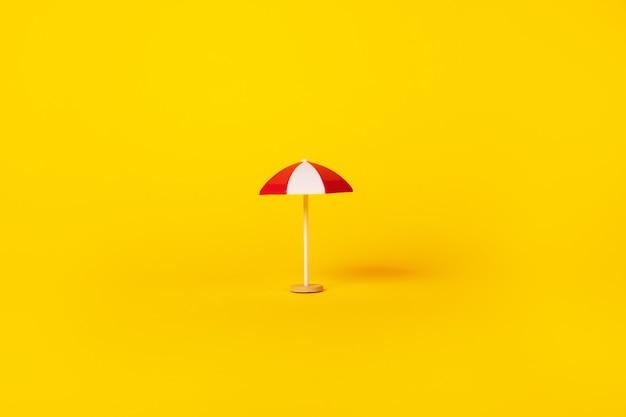 Czerwono-biały parasol plażowy na żółtym tle, koncepcja lato i wakacje