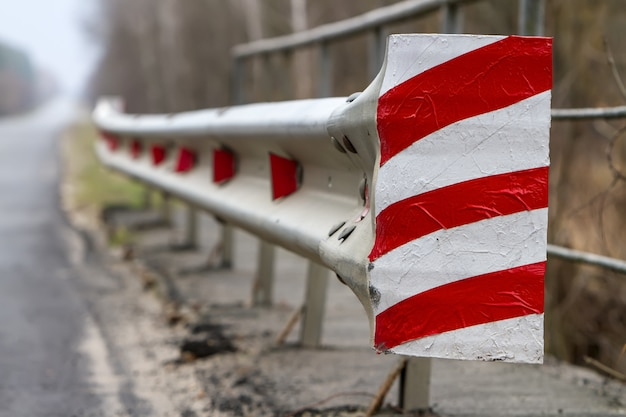 Czerwono-biały płot z odblaskami czerwonego światła wzdłuż drogi