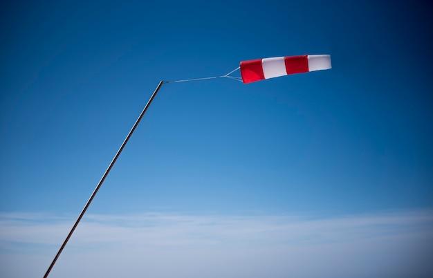 Czerwono-biały wskaźnik wiatru na tle błękitnego nieba