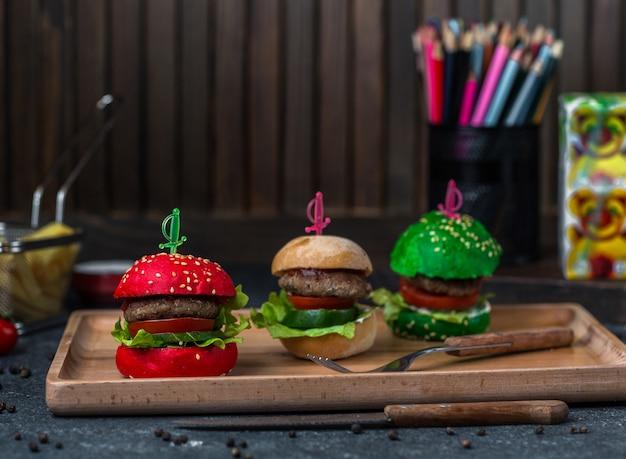 Czerwono-brązowe i zielone chlebowe burgery z bułki na tacy.