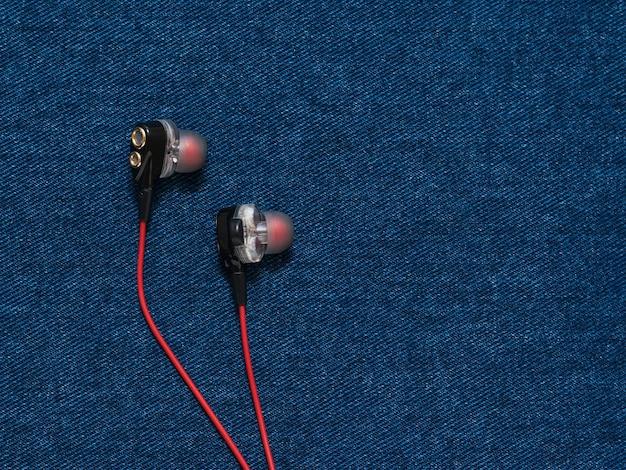 Czerwono-czarne słuchawki na płaskim dżinsowym tle. modny styl młodzieżowy.