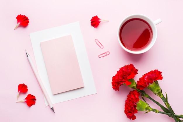 Czerwono-różowe przedmioty. filiżanka herbaty, kwiaty goździka notatnik dla tekstu na pastelowym różowym tle.