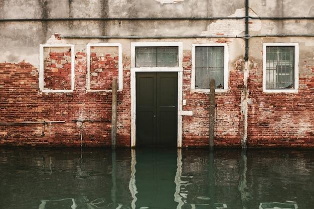 Czerwono-szary betonowy dom z czarnymi drewnianymi drzwiami