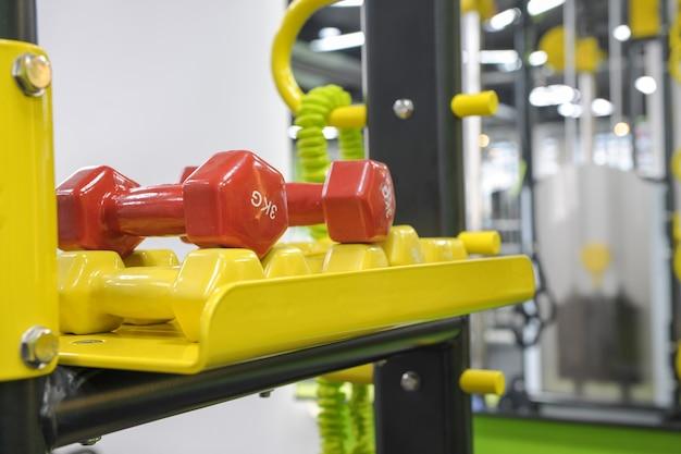Czerwono-żółte hantle sportowe i kettlebells na zbliżenie na stoisku