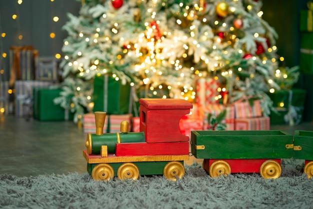 Czerwonozielony drewniany pociąg pod choinką koncepcja wesołych świąt i szczęśliwego nowego roku
