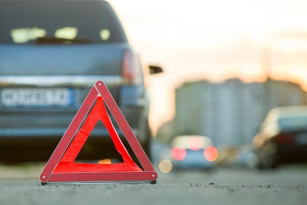 Czerwony awaryjny trójkąt znak stop i uszkodzony samochód na ulicy miasta.
