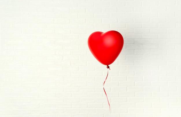 Czerwony ballon z kształtem serca wisi aganst białej ścianie