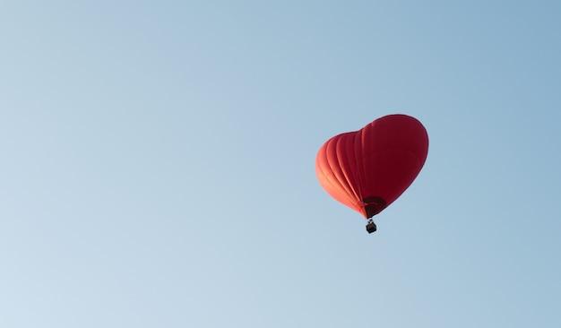 Czerwony balon w kształcie serca. rozrywka lotnicza. loty balonem na ogrzane powietrze.