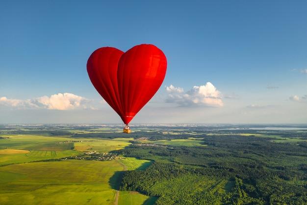 Czerwony balon w kształcie serca z ludźmi nad zielonymi polami i lasami.