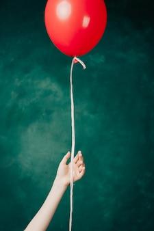 Czerwony balon w ręku na zielonym tle leci z bliska