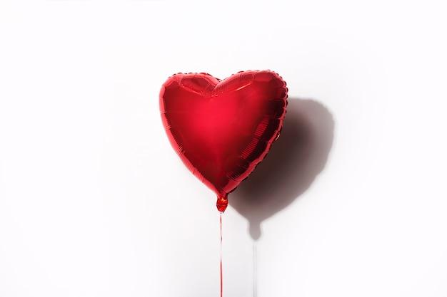 Czerwony balonik w formie serca na białym tle.