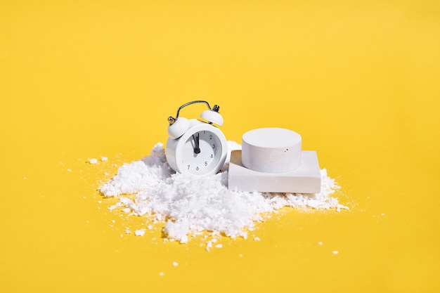 Czerwony biały budzik ze śniegiem na żółtym tle i podium dla produktu. kreatywna wyprzedaż świąteczna. wysokiej jakości zdjęcie