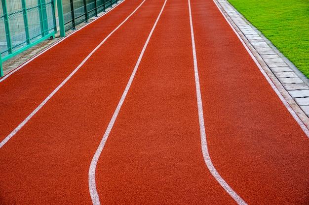 Czerwony bieżnia z białymi liniami w odkrytym stadionie sportowym, po stronie jest pole i park.