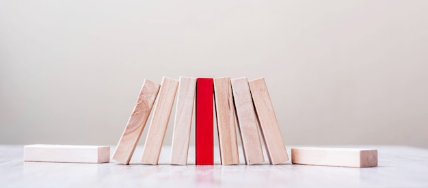 Czerwony blok i drewniane bloki stoją na stole. praca zespołowa, wspólność, zarządzanie ryzykiem, rozwiązanie, lider, strategia, różne i unikalne koncepcje
