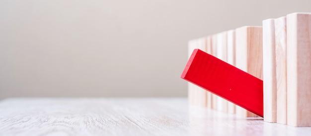 Czerwony blok wyróżnia się z tłumu drewnianych klocków. różne, unikalne i ludzkie zarządzanie zasobami, przywództwo, rasizm