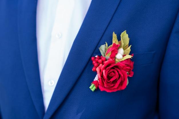 Czerwony boutonniere na niebieskiej kurtce.