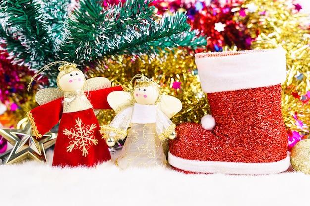 Czerwony bucik świętego mikołaja i bożonarodzeniowa lalka ze świątecznymi ozdobami i dekoracjami