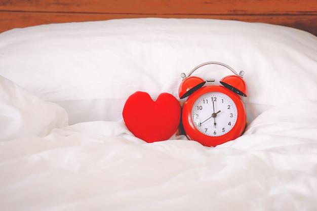 Czerwony budzik i czerwony kształt serca na łóżku w domu
