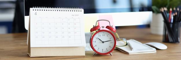 Czerwony budzik i kalendarz do zadań planowania na pulpicie dla koncepcji z miesięcznym wyprzedzeniem