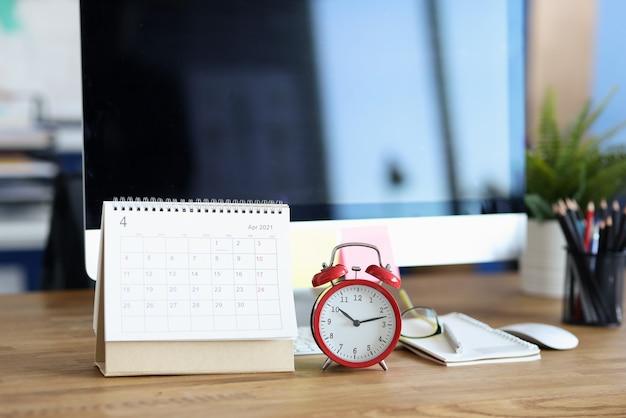 Czerwony budzik i kalendarz na pulpicie