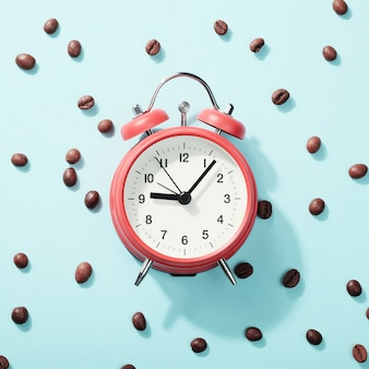 Czerwony budzik i palone ziarna kawy na niebiesko z cieniem. pojęcie przebudzenia rano, początek dnia roboczego