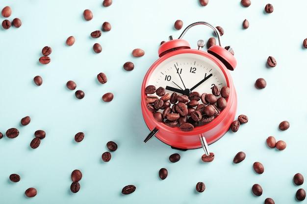 Czerwony budzik i palone ziarna kawy