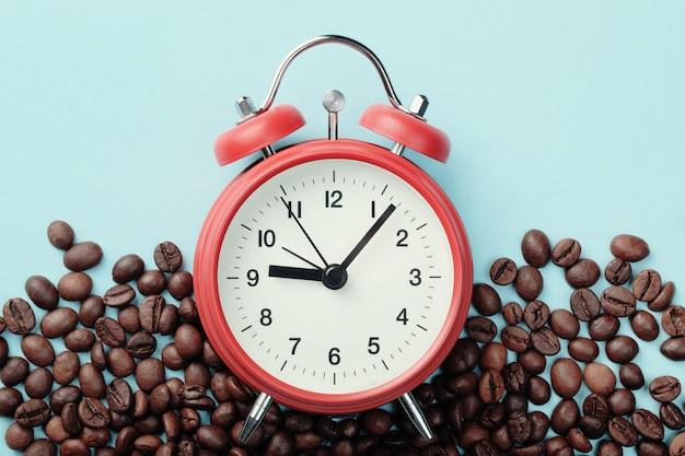 Czerwony budzik i palonych ziaren kawy na niebieskim stole