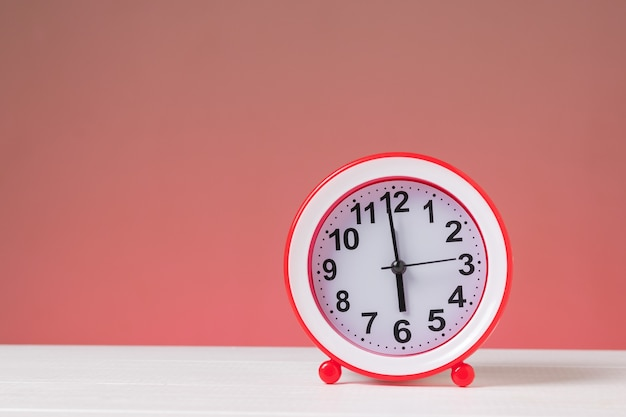 Czerwony budzik na białym stole na czerwonym tle. klasyczny zegar analogowy.