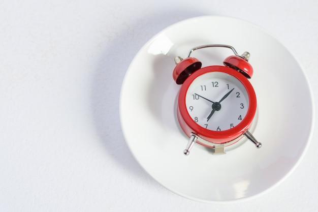 Czerwony budzik na białym talerzu ze srebrną łyżeczką