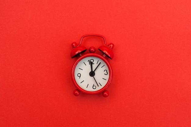 Czerwony budzik na czerwonym tle