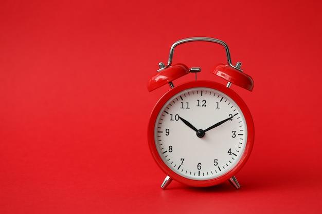 Czerwony budzik pokazuje 10 godzin rocznika nowoczesnego